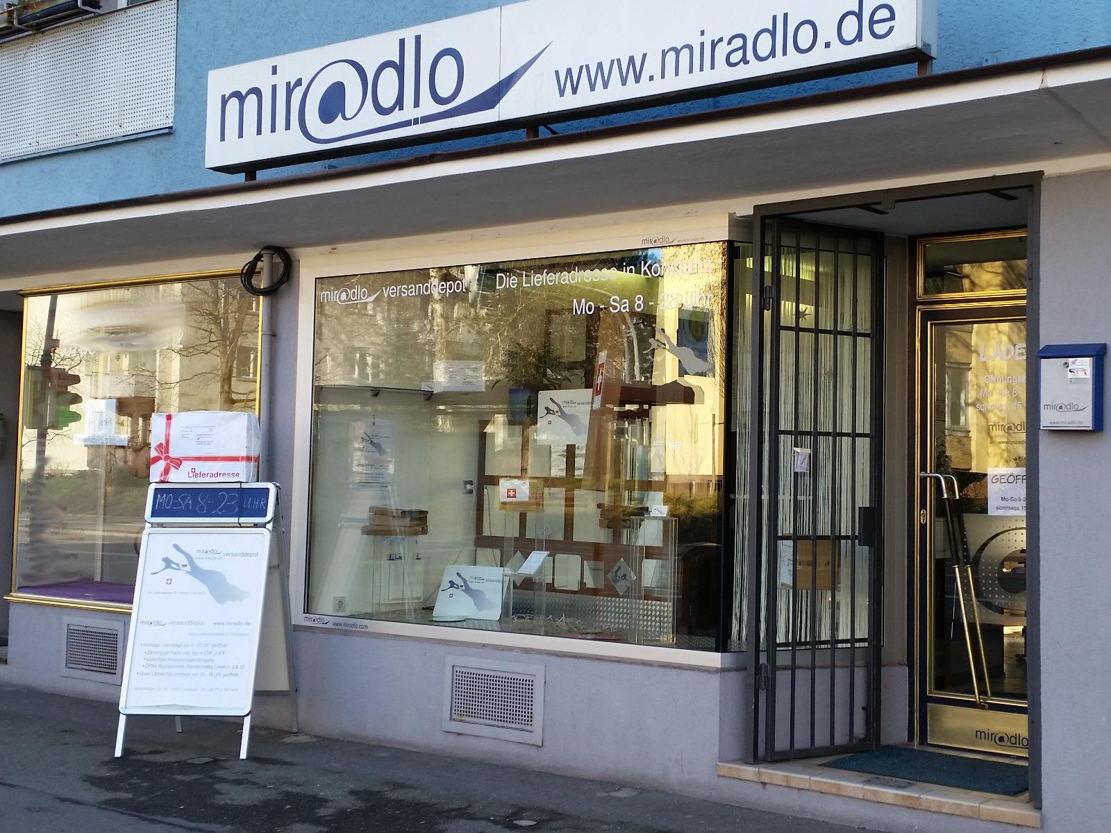 Vorm Schaufenster unser Plakatständer, auf dem oben ein Paket steht. miradlo-Versanddepot in Konstanz