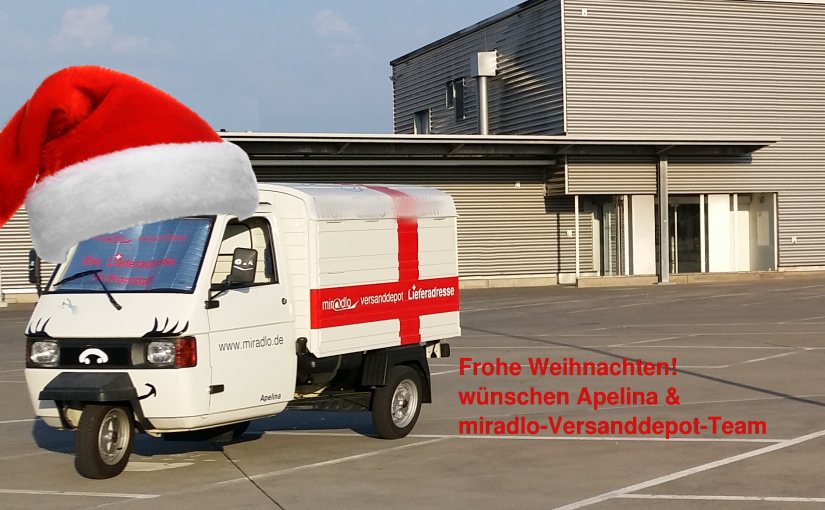 Frohe Weihnachten wünschen Apelina und das miradlo-Versanddepot-Team, mit Weihnachtsmützen-Apelina