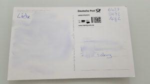 Postkarte mit Handyporto Aufkleber der Post neben dem 12-stelligen Code